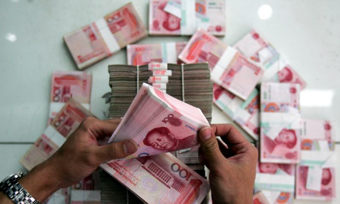 A clerk counts stacks of Chinese yuan at a bank in Beijing, China, on July 22, 2005. (China Photos/Getty Images)