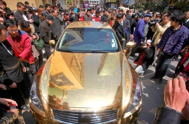 A gold-plated Infiniti luxury sports car outside a jewelry store in Nanjing, in East China's Jiangsu Province, March 31, 2011. (STR/AFP/Getty Images)
