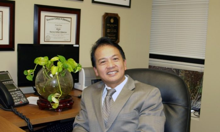 Dr. Loc T. Le sits at his office in Maryland in 2012. (The Epoch Times)
