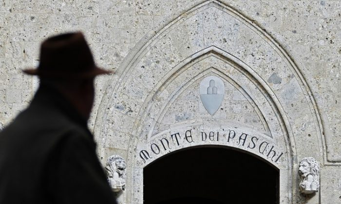 A man walks past the headquarters of the Banca Monte dei Paschi di Siena, the world's oldest bank, on Jan. 25. has to secure a €5 billion capital to survive. (Fabio Muzzi/AFP/Getty Images)