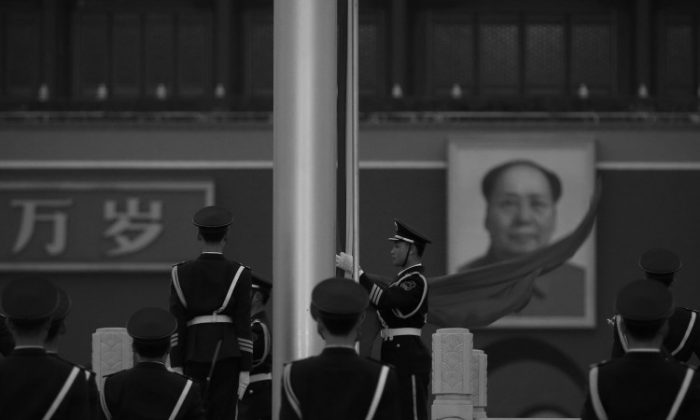 A paramilitary police officer collects the PRC flag in front of Mao Zedong's portrait in Beijing's Tiananmen Square on March 2. China Central Television recently quoted Mao saying that he was willing to see hundreds of millions of Chinese killed. (Feng Li/Getty Images)