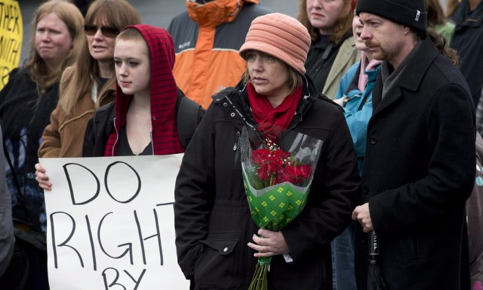 Leah Parsons, mother of Rehtaeh Parsons, and her partner Jason Barnes (R), attend a protest near the Halifax Regional Police headquarters in Halifax on April 14, 2013. Rehtaeh Parsons ended her own life following months of bullying after she was allegedly sexually assaulted by four boys and a photo of the incident was distributed online. (The Canadian Press/Andrew Vaughan)