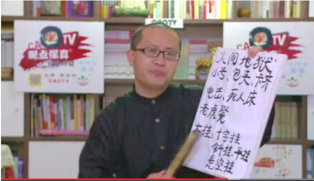 Cao Baoyin held up a board with the names of torture methods used at the Masanjia Labor Camp. He was supposed to do a web show about an economic forum, but poured his heart out over the reports of extreme torture. (Screenshot via The Epoch Times)