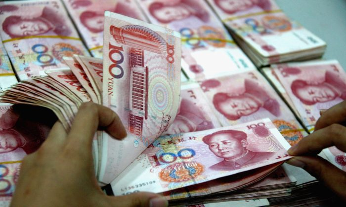 A staff member counts money at a Chinese bank, on April 18, 2011. (ChinaFotoPress/Getty Images)