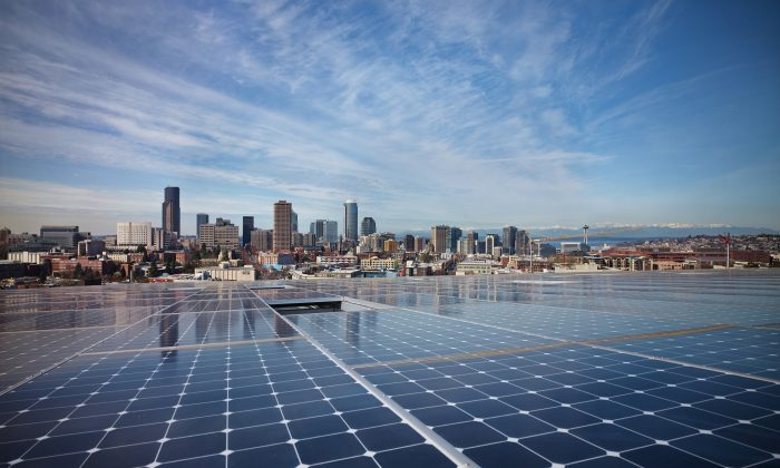 Solar panels line the roof of the Bullitt Center with its view of Seattle seen in the distance. The center had been designed to meet the stringent requirements of a Living Building. (Ben Benschneider)