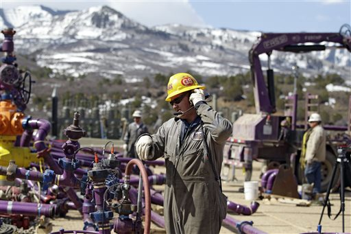 A worker uses a headset and microphone to communicate with coworkers over the din of pump trucks, at the site of a natural gas hydraulic fracturing and extraction operation run by the Encana Oil & Gas (USA) Inc., outside Rifle, in western Colorado. (AP Photo/Brennan Linsley)