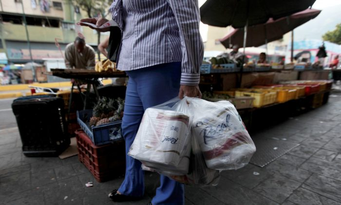 A woman who just bought toilet paper at a grocery store reads her receipt as she leaves the private store in Caracas, Venezuela, on May 15, 2013. First milk, butter, coffee, and cornmeal ran short. Now Venezuela is running out of the most basic of necessities—toilet paper. Economists say Venezuela's shortages stem from price controls meant to make basic goods available to the poorest parts of society and the government's controls on foreign currency. (AP Photo/Fernando Llano)