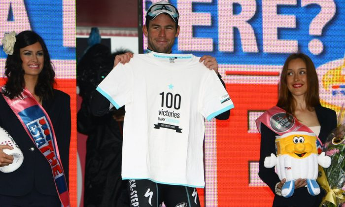 Mark Cavendish of Omega Pharma-Quickstep displays a T-shirt commemorating his 100th professional win after sprinting to victory in Stage Twelve of the 2013 Giro d'Itlia. (omegapharma-quickstep.com)