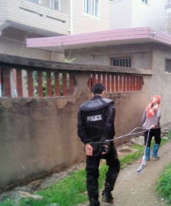 A woman leads a police officer captured after a standoff with authorities over land grabs in Dongwiao Town, Fujian Province, on May 11, 2013. (molihua.org)