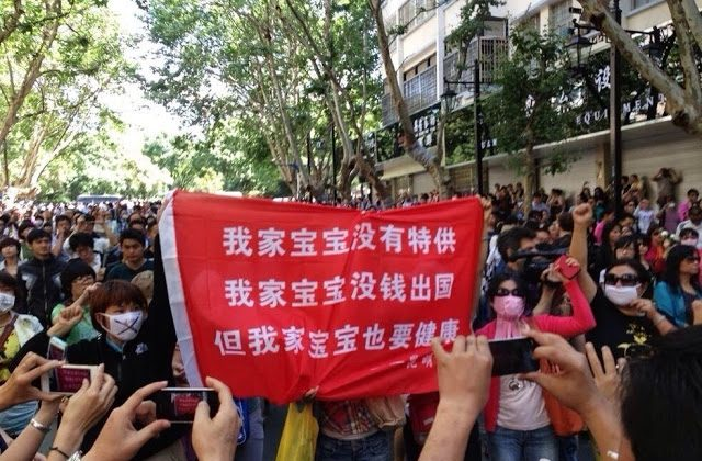 "Protesters hold up a banner about pollution, comparing their situation with that of communist officials. ""My child doesn't have a special supply of clean air, water or food, my child doesn't have money to go abroad, but my child needs to be healthy too!"" (Weibo.com) This is what saying on the red banner."