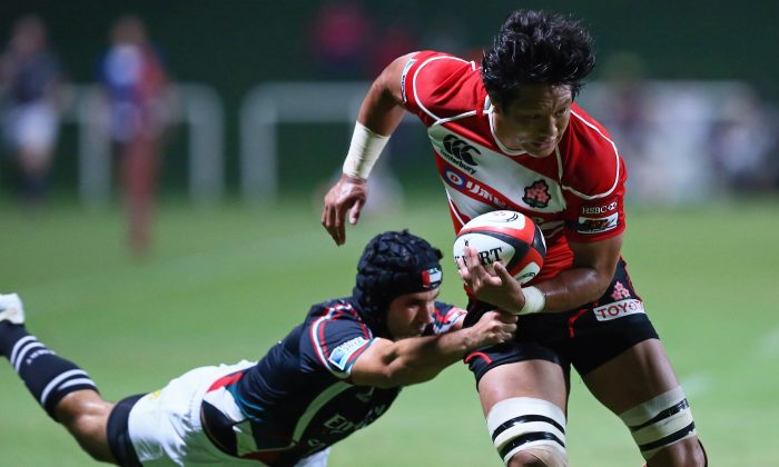 Japan's Takashi Kikutani escapes a tackle during the Asian Five Nations rugby match against UAE at the Sevens stadium in the Gulf emirate of Dubai on May 10, 2013. Japan's dominant 93-3 victory over UAE gave them a clean sweep in the series. (MARWAN NAAMANI/AFP/Getty Images)