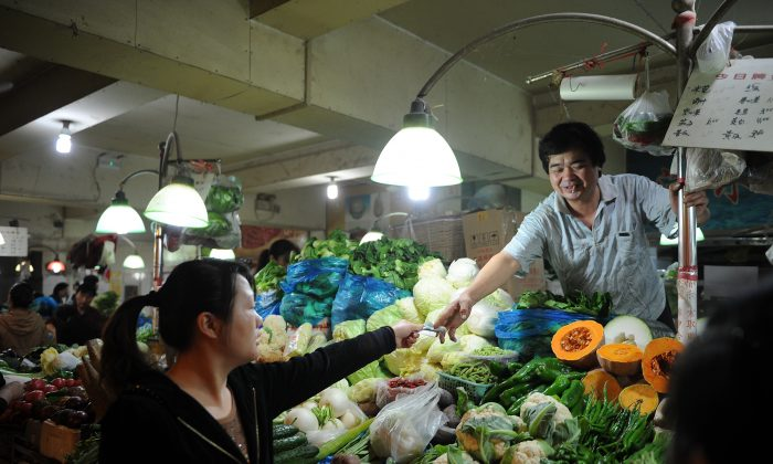 A vendor sells vegetables in a market in Shanghai on Oct. 18, 2012. Prices for inputs are rising across the country, squeezing ordinary Chinese people, according to recent economic statistics and expert analysis. (Peter Parks/AFP/Getty Images)