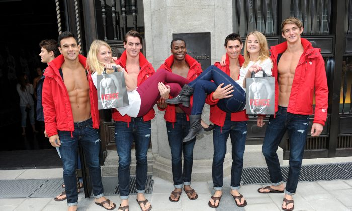"Young women pose for photographs with male models outside the Abercrombie & Fitch flagship clothing store during the opening of Abercrombie & Fitch Munich flagship store on October 25, 2012 in Munich, Germany. The clothing company has been criticized for catering to ""cool, good-looking people."" (Hannes Magerstaedt/Getty Images)"