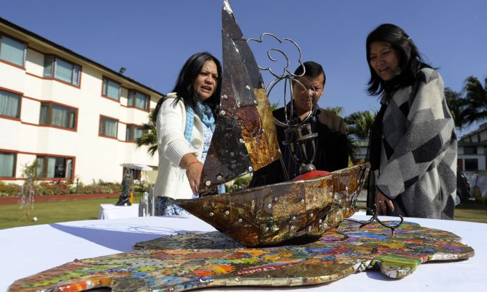 Visitors look at art made from trash collected on Mount Everest, in Kathmandu. Discarded oxygen and cooking gas cylinders, ropes, tents, glasses, beer cans, plastic and even the remains of a helicopter make up 75 artworks commissioned for the 'Everest 8848 Art Project' on display in Kathmandu. (PRAKASH MATHEMA/AFP/Getty Images)