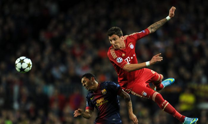 Barcelona's Brazilian defender Adriano (L) vies with Bayern Munich's Croatian striker Mario Mandzukic during the UEFA Champions League semi-final match FC Barcelona vs FC Bayern Munich on May 1, 2013. (LLuis Gene/AFP/Getty Images)