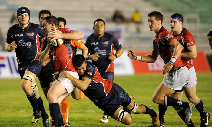 Philippines threw everything they had at Hong Kong, but the Hong Kong pack overcame the early resistance to produce a winning second half ... Alexander Baddeley of Hong Kong is tackled by Philippine's Olivier Patrice during their Rugby Asian 5-Nations match at the Rizal Memorial Stadium in Manila on May 4. (NOEL CELIS/AFP/Getty Images)
