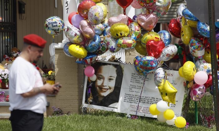 A Guardian Angel waits for the car carrying kidnap victim Gina DeJesus to arrive at her house on May 8, 2013, in Cleveland, Ohio. DeJesus was one of three women who were held captive for almost a decade in a home in Cleveland. (Matt Sullivan/Getty Images)