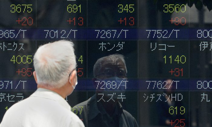 Pedestrians walk past an electric quotation board displaying the Nikkei key index of the Tokyo Stock Exchange (TSE) in front of a securities company in Tokyo on May 10, 2013. (Toru Yamanaka/AFP/Getty Images)
