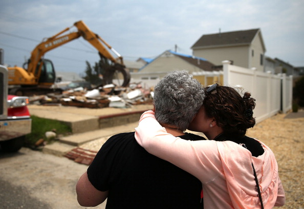 ORTLEY BEACH, NJ - MAY 15: Denise Avrutik (L), gets a hug from her daughter Julianne Avrutik as they watch their home get demolished after it was damaged six months ago by Superstorm Sandy, May 15, 2013 in Ortley Beach, New Jersey. Mrs. Avrutik's family has owned the home since 1959 when she was only three years old. The neighboring town of Mantoloking had all 528 homes either damaged or destroyed by the storm and say that at least 50 homes are scheduled to be demolished in the up coming weeks. (Photo by Mark Wilson/Getty Images)
