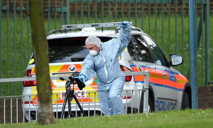 A forensic police offer photographs evidence at the scene where a soldier was butchered to death with a machete, in what officials are treating as a terrorist attack (Dan Kitwood/Getty Images)