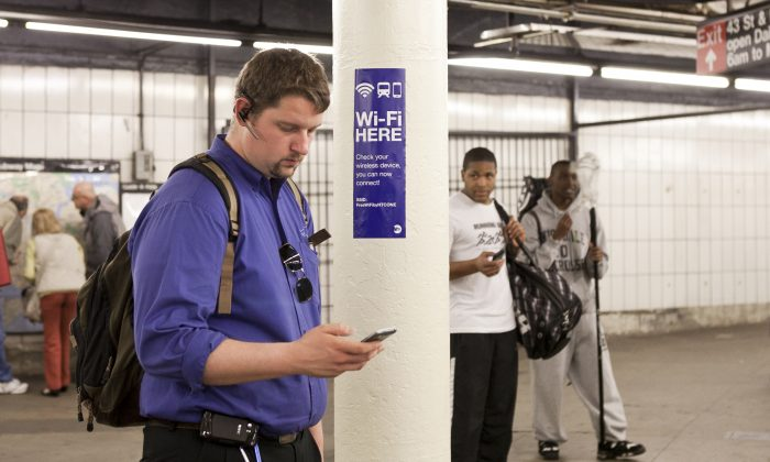 A commuter uses his smartphone in the Times Square subway platform on April 25. The Manhattan DA is asking smart phone manufacturers to take action to quell phone theft.  (Samira Bouaou/Epoch Times)