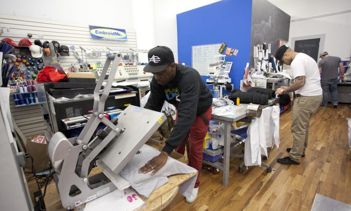 Stanley Nozil and Marcos Peralta work on customizing garments at EmbroidMe on May 2 in Midtown Manhattan. The shop specializes in customized embroidery, and garment and screen printing. (Samira Bouaou/The Epoch Times)