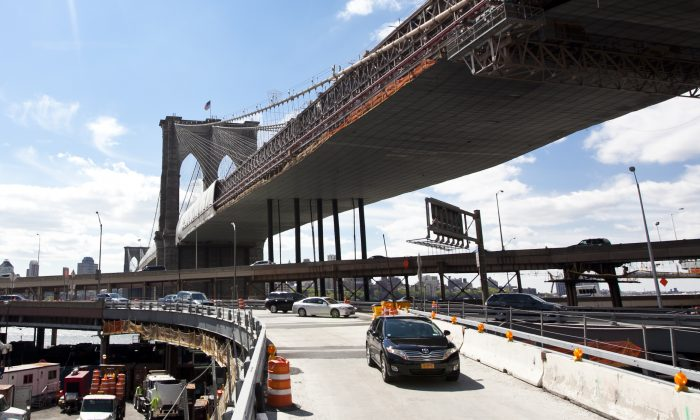 Cars enter the Brooklyn Bridge and Manhattan's Civic Center at a fork on a newly-expanded ramp onto the Brooklyn Bridge. In the background, the Brooklyn Bridge is covered with tarp and scaffolding as it is being repainted. The new ramp and the repainting are part of a $508 million renovation of the Brooklyn Bridge. (Samira Bouaou/Epoch Times)