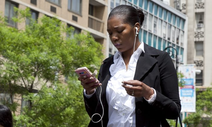 A woman checks her iPhone while walking in New York City. (Samira Bouaou/The Epoch Times)