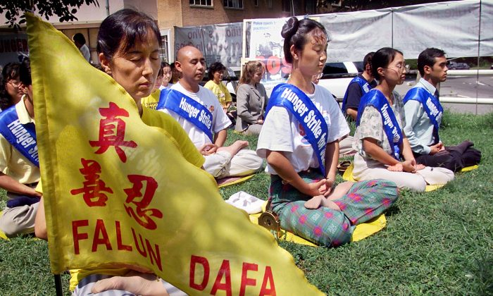 Falun Gong practitioners meditate as they enter their fourth day of a hunger strike in front of the Chinese Embassy in Washington, D.C., on Aug. 20, 2001. The practitioners held the hunger strike to call for the release of 130 practitioners imprisoned at the Masanjia Labor Camp in Liaoning Province of China. (STEPHEN JAFFE/AFP/Getty Images)
