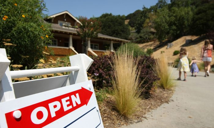 A sign advertising an open house is posted outside a home for sale in this file photo. With a lack of inventory to meet buyer demand, brokers are changing their business approaches. (Justin Sullivan/Getty Images)