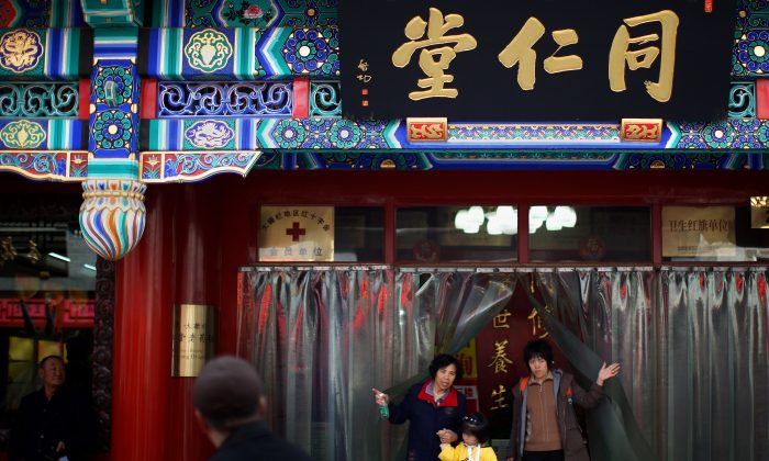 Chinese residents walk out of the Tongrentang drugstore, the famous Chinese traditional medicine drugstore, in an alleyway of the Qianmen area on March 16, 2008 in Beijing, China. (Feng Li/Getty Images)