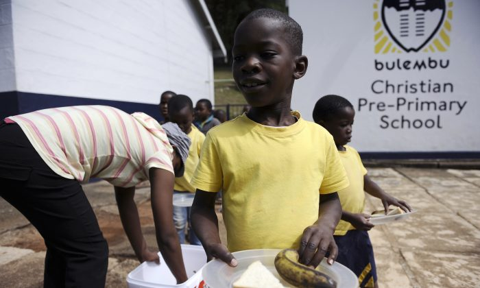A boy holds a plate as pupils queue for lunch in a school for children orphaned by AIDS on March 1, 2012 in the town of Bulembu in Swaziland. Swaziland has the world's highest rate of HIV infection, with at least one in four adults carrying the virus, and about 120,000 children have been orphaned, comprising more than 10 percent of the total population. (Stephane de Sakutin/AFP/Getty Images)