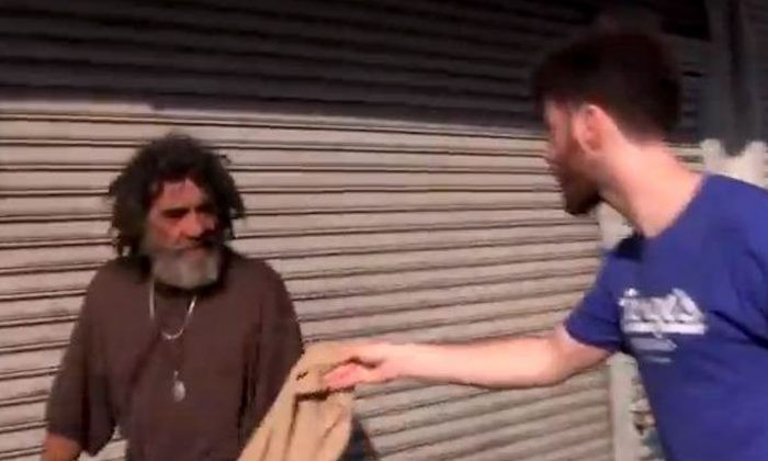 Filmmaker Greg Karber hands a man a piece of Abercrombie & Fitch clothing in East Los Angeles in a video posted to YouTube on May 13, 2013. (Screenshot/YouTube)