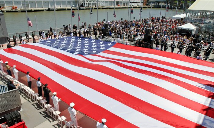 A giant American flag is unveiled on the U.S.S. Intrepid in New York during a Memorial Day ceremony on May 27. (Joshua Philipp/The Epoch Times)