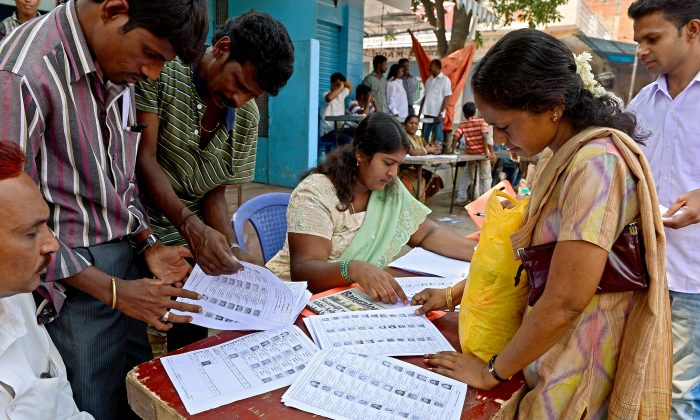 Indian voters check their names on a voters list near a polling booth during state assembly elections in Bangalore on May 5, 2013. As state elections take place across India throughout the year, activists worry about the impact of rampant list errors and obstacles to registration on democracy in India. (Manjunath Kiran/AFP/Getty Images)