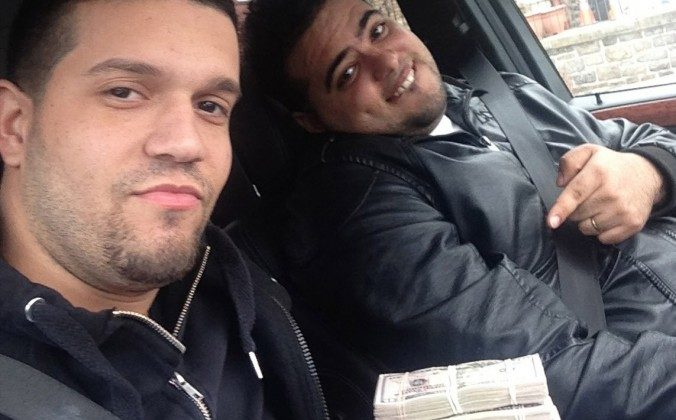 In this undated photo provided by the United States Attorney's Office for the Southern District of New York, Elvis Rafael Rodriguez, left, and Emir Yasser Yeje, pose with bundles of cash allegedly stolen using bogus magnetic swipe cards at cash machines throughout New York. (AP Photos/U.S. Attorney's Office for the Southern District of New York)