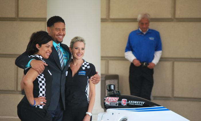 Thais Jackson and Kathy Flick with the Baltimore Grand Prix John S. Holt III pose for a photo with an IZOD Indy Car Series car at the MD. Washington Minority Companies Association Spring Breakfast and business expo in Balitore on May 10. (Ron Dory/The Epoch Times)