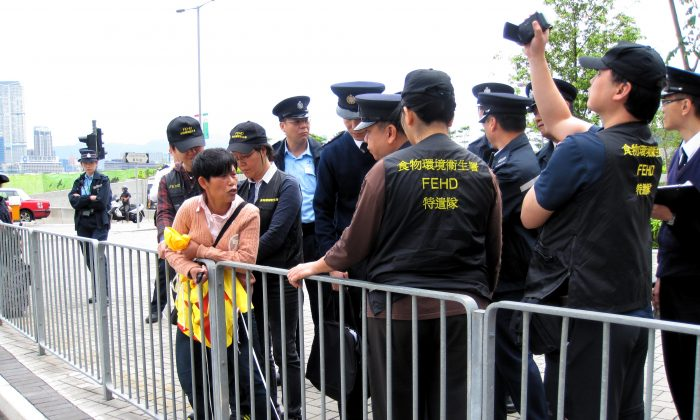 A Falun Gong practitioner is surrounded by members of the Food and Environmental Hygiene Department, along with police, outside the Central Government Complex at Tamar in Hong Kong on May 2. The authorities arrested the practitioner, an unusual action, after she refused to yield a fourth banner. (Bill Cox/The Epoch Times)