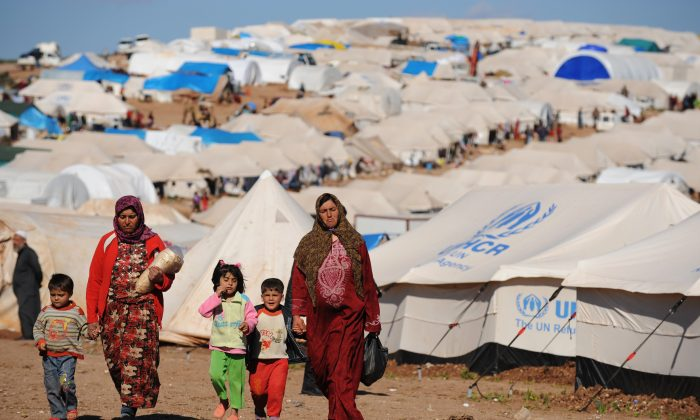 Syrian internally displaced people walk in the Atme camp, along the Turkish border in the northwestern Syrian province of Idlib, on March 19, 2013. (Bulent Kilic/AFP/Getty Images)
