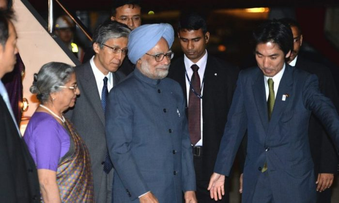 Indian Prime Minister Manmohan Singh (C), accompanied by his wife Gursharan Kaur (L), is greeted by a Japanese official upon his arrival at Tokyo International Airport on May 27, 2013. Singh is here on a three-day visit to have talks with his Japanese counterpart Shinzo Abe to strengthen strategic and global partnership between both countries. (Yoshikazu Tsuno/AFP/Getty Images)