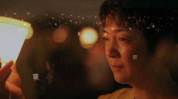 """Jennifer Zeng sits at a candlelight vigil held for persecuted and killed Falun Gong practitioners in China. Zeng's story is told in """"Free China: The Freedom to Believe,"""" which will be in theaters in Los Angeles on May 31 and in New York on June 7. (Screenshot from """"Free China"""" trailer)"""