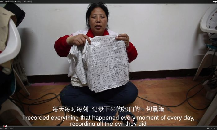 "Liu Hua holds up the diaries of torture and abuse that she had smuggled from the labor camp. After saying the line that appears in the subtitle in this picture, she said: ""And had the women smuggled it out their vaginas."" (Screenshot via The Epoch Times)"