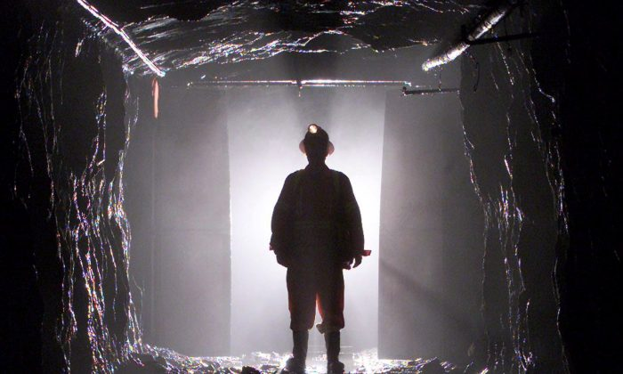 A miner is silhouetted as he passes through a doorway in a mine shaft 100 feet below the surface. Migrant workers, such as in HD Mining's controversial decision to hire some 200 Chinese miners to work in B.C., are filling the majority of new jobs created in Canada in recent years, a new study has found. (THE CANADIAN PRESS/Adrian Wyld)