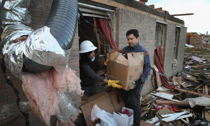 Ofelia Olivera (L) and Oscar Ruiz help to salvage items from a friend's home after a powerful tornado ripped through the area in Moore, Okla., on May 21, 2013. (Scott Olson/Getty Images)