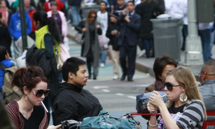 Katherin Burns, 19, left, smokes with Shannon Roy, 18, right, in the pedestrian plaza in Times Square in New York in a Feb. 18, 2011 file photo. (AP Photo/Frank Franklin II)