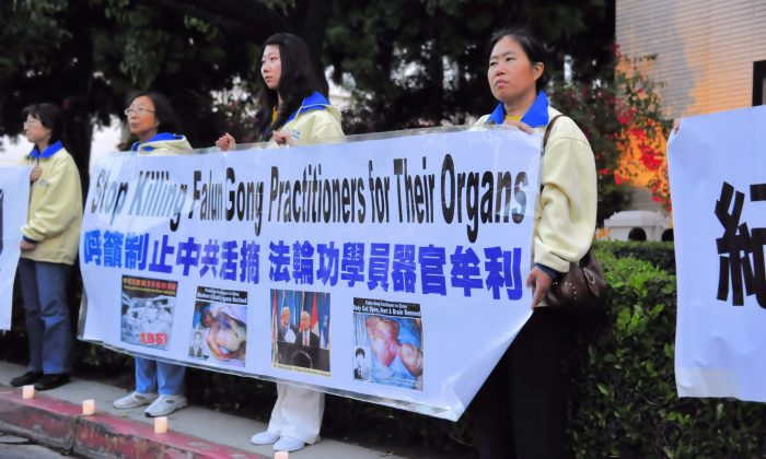 Falun Dafa practitioners hold a banner at the curb at the LA Chinese Consulate demanding the cessation of live organ harvesting from Falun Dafa Practitioners in China. (Epoch Times)