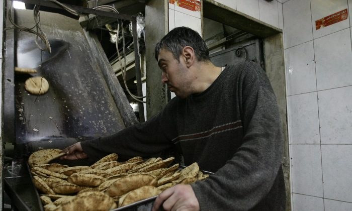 An employee puts pastries on a tray at a bakery in the Syrian capital Damascus on March 7, 2013. The nation's bakeries have lost a total of more than $3.5 million since the civil war began. (Louai Beshara/AFP/Getty Images)