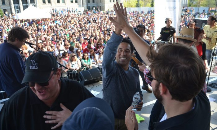 """""""The Office"""" parade: Actor Oscar Nunez (C) high-fives cast mate John Krasinski after singing on stage during """"The Office"""" Wrap Party in Scranton, Pa. on Saturday, May 4, 2013.(AP Photo/Scranton Times & Tribune, Jason Farmer)"""