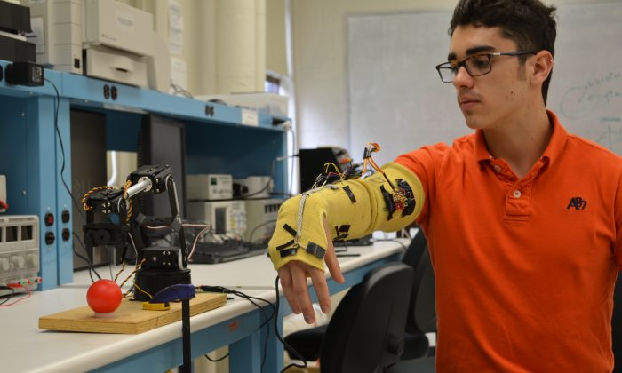 Vinicius Bazan, an exchange student from Brazil at the Polytechnic Institute of New York University, wears an electronic sleeve that lets him control a robotic arm. Students in New York City's technology schools will be among the first pioneers of the city's new focus on a technology economy. (Courtesy of Jared Frank)