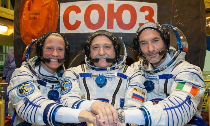"""In the Integration Facility at the Baikonur Cosmodrome in Kazakhstan, Expedition 36/37 Flight Engineer Karen Nyberg of NASA (left), Soyuz Commander Fyodor Yurchikhin (center) and Flight Engineer Luca Parmitano of the European Space Agency (right) pose for pictures during a suited dress rehearsal """"fit check"""" exercise May 17. The trio will launch May 29, Kazakh time (May 28 EDT), in their Soyuz TMA-09M spacecraft to begin a 5 ½ month mission on the International Space Station. (NASA/Victor Zelentsov)"""